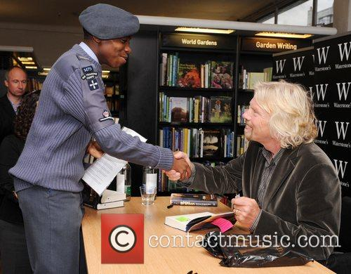 Signs copies of his book 'Business Stripped Bare:...