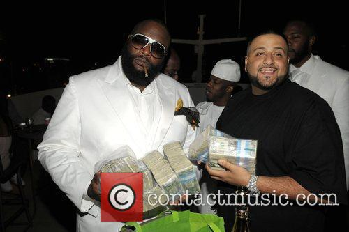 Rick Ross and DJ Khaled hold a stacks...