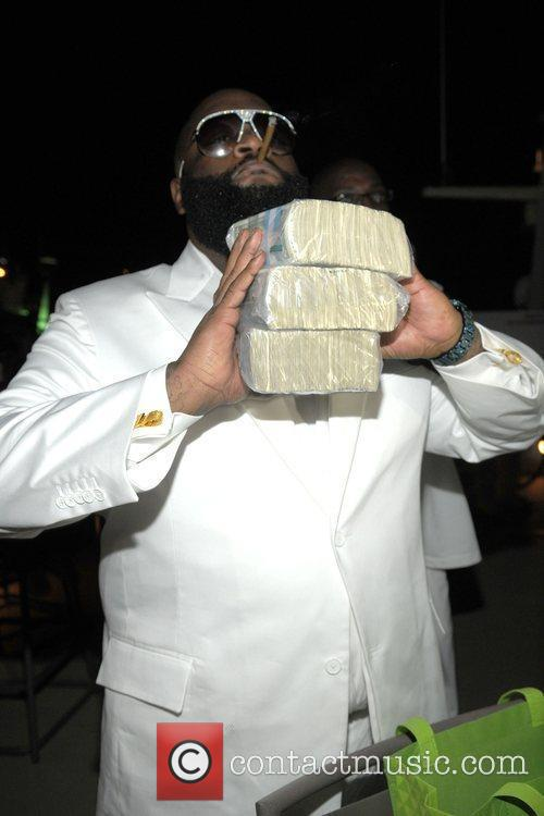 Rick Ross holds a stack of one dollar...