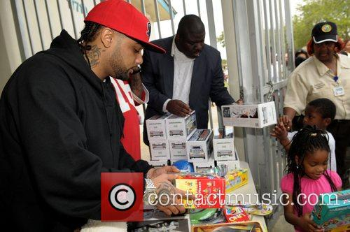 Hands out gifts during the Rick Ross Charities...
