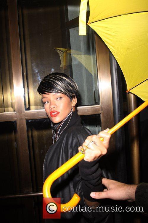 Singer Rihanna standing under her umbrella as she...