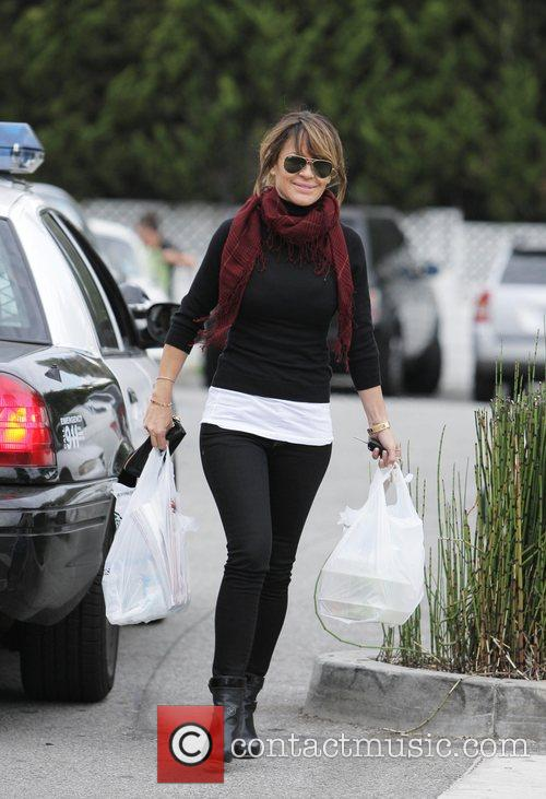 Leaves Bristol Farms store with her groceries in