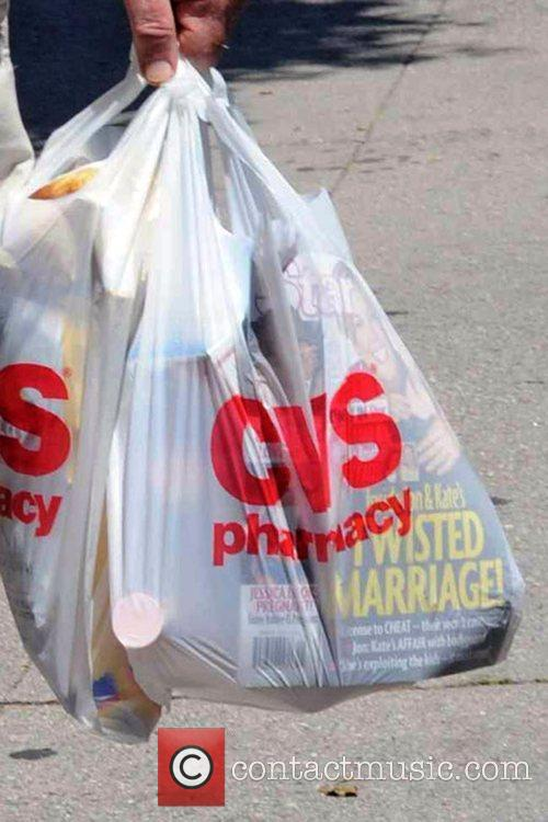 Leaves CVS pharmacy after purchasing a tabloid magazine...