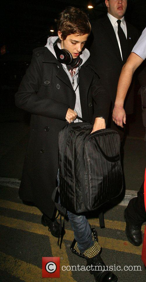 Carries her suitcase as she arrives at Heathrow...