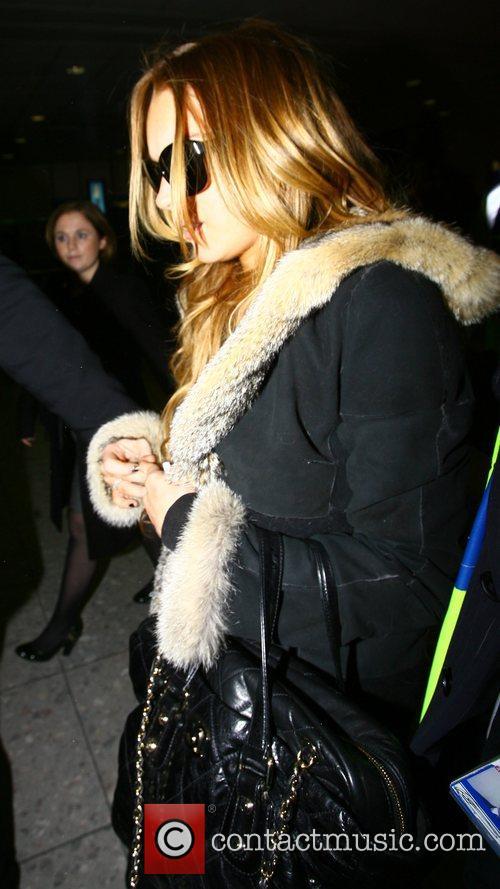 Lindsay Lohan Walks through Heathrow Airport after arriving...