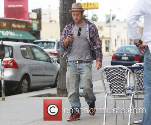 Scott Caan checks his mobile device while leaving...