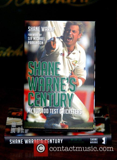 Signs copies of his new book 'Shane Warne's...