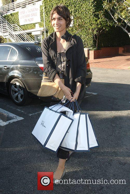 Carrying a handful of shopping bags as she...