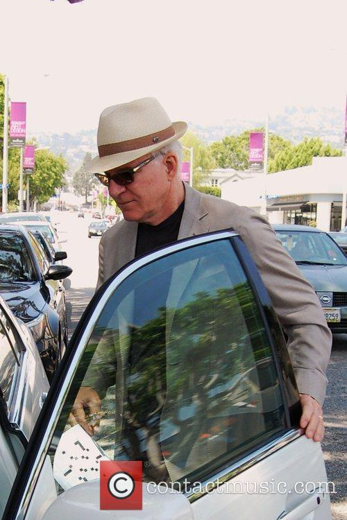Steve Martin leaves Il Piccolino restaurant carrying a...