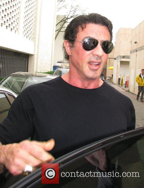 Sylvester Stallone  leaving Le Grand Passage carrying...