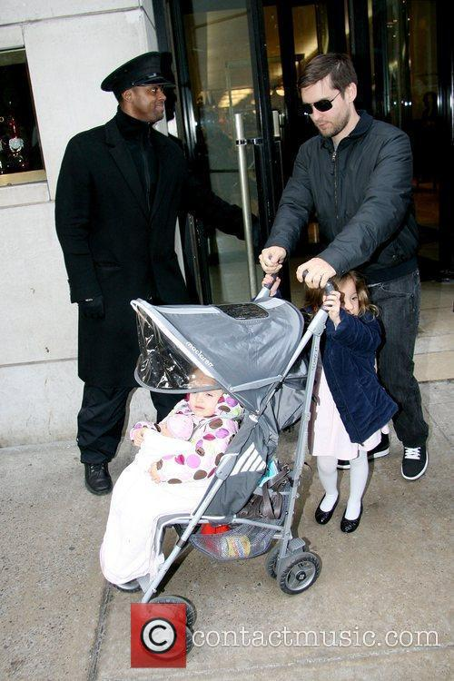 Pushes a stroller with his daughter Ruby Maguire...