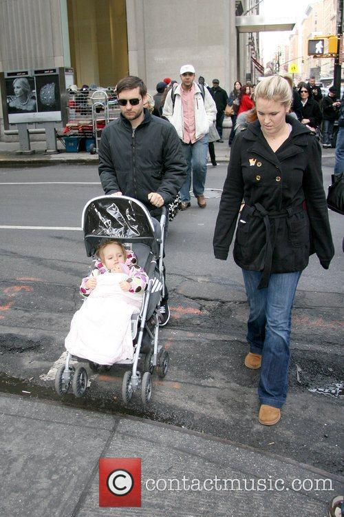 Tobey Maguire pushes a stroller with his daughter...
