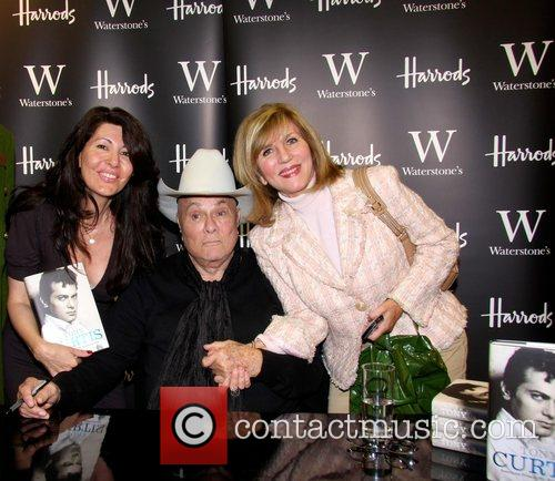 Signs copies of his autobiography 'American Prince' at...