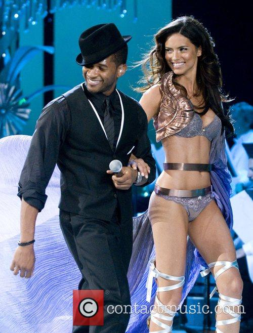 A Victoria Secret model with Usher walks the...