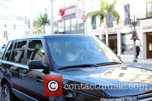 Driving his black Range Rover along Rodeo Blvd.