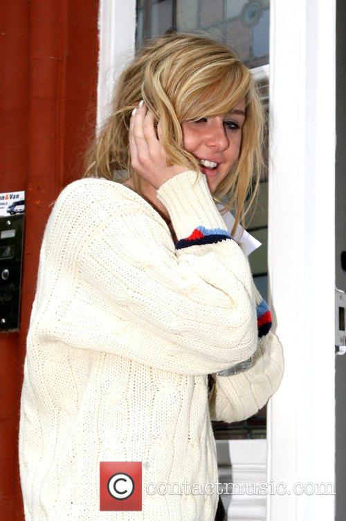 Talks on the phone as she returns to...