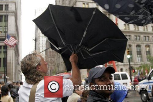 Atmosphere An onlooker struggles with his umbrella in...