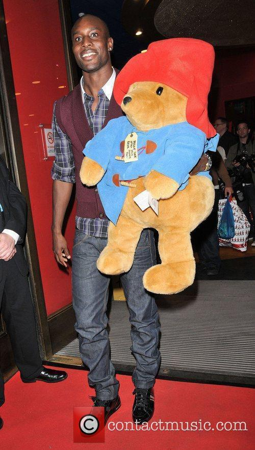 Holds a big Paddington Bear soft toy as...