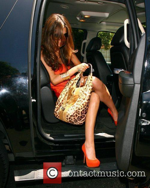 Arriving at a studio wearing a bright orange...