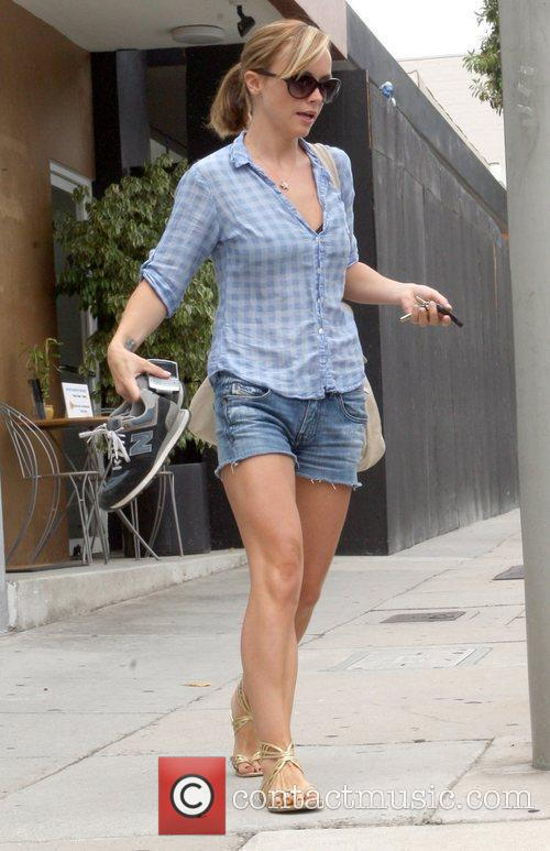 Christina Ricci holding her New Balance sneakers while...