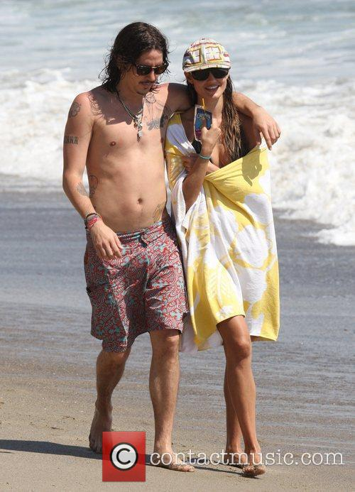 Takes a walk along Malibu beach with his...