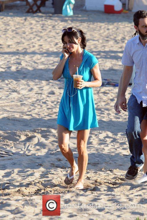 Courteney Cox talks on her phone while on...
