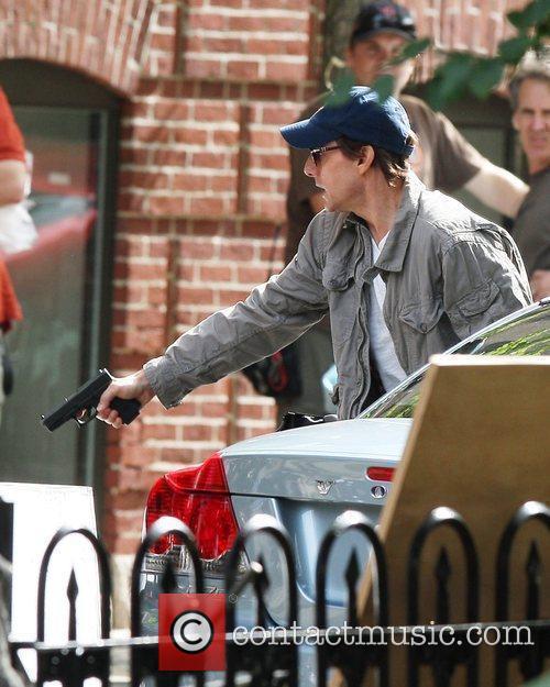 Tom Cruise aims a gun on the set...