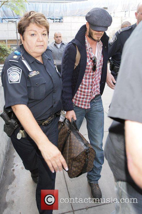 David Beckham, carrying his Louis Vuitton travel bag,...