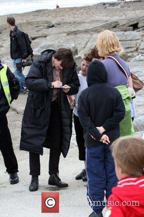 Matt Smith sign autographs for fan while on...
