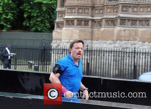 Eddie Izzard jogs past the Houses of Parliament