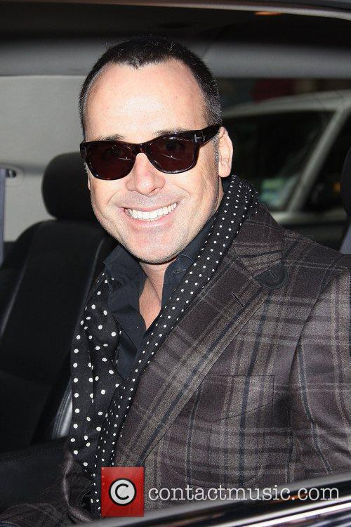 David Furnish smiles for the camera while leaving...