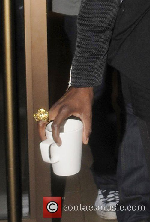 Leaving her hotel carrying a mug