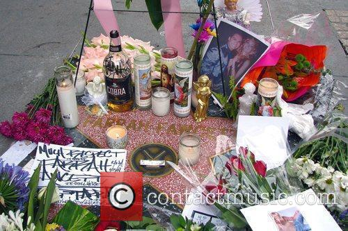 More flowers and candles adorn Farrah Fawcett's star...
