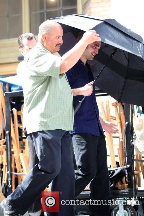 Robert Pattinson tries to hide under an umbrella...