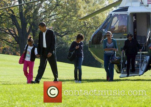 With his wife Michelle and their daughters Malia...