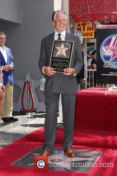 George Hamilton  poses with a plaque after...