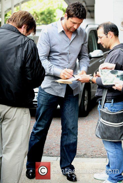 Signs autographs for fans as he leaves the...
