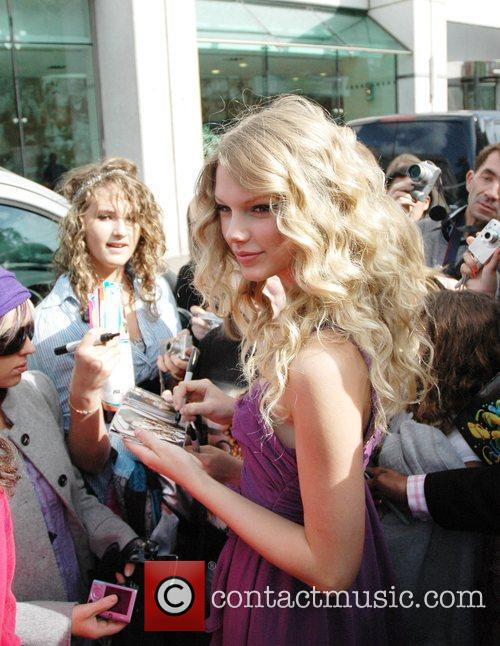 Taylor Swift signs autographs for fans as she...