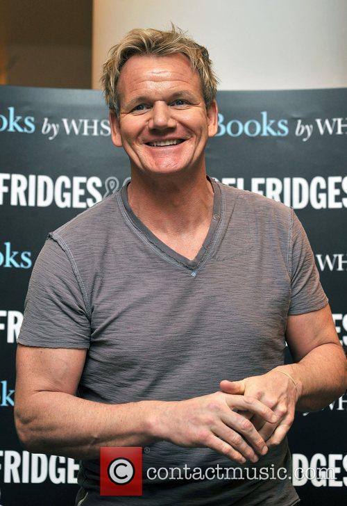 Signs his book 'Gordon Ramsay's World Kitchen' at...