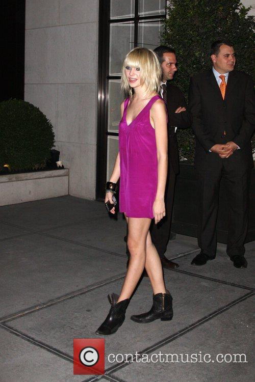 Poses for photographs outside her hotel after a...