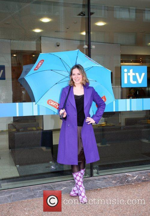 Poses with a 'GMTV' umbrella outside the ITV...