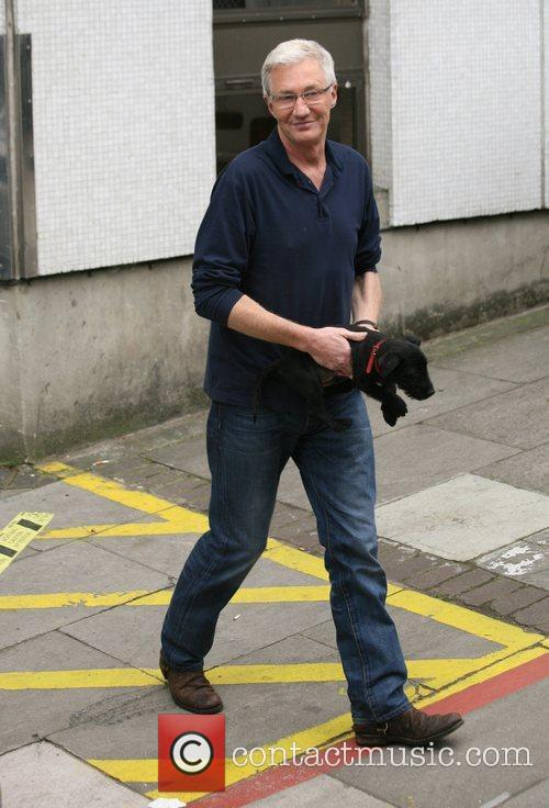 Paul O'Grady carrying a puppy while leaving the...