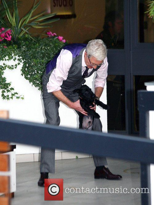 Paul O'Grady seen lifting a dog outside the...