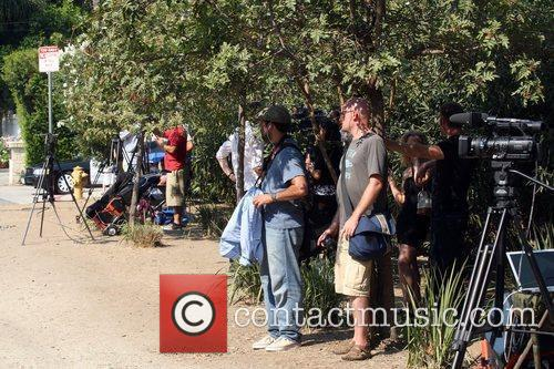 Media crews converge outside the Encino residence of...