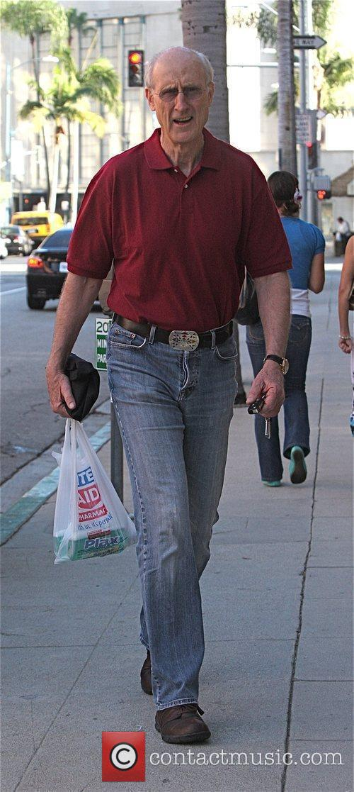 James Cromwell carrying a plastic shopping bag after...