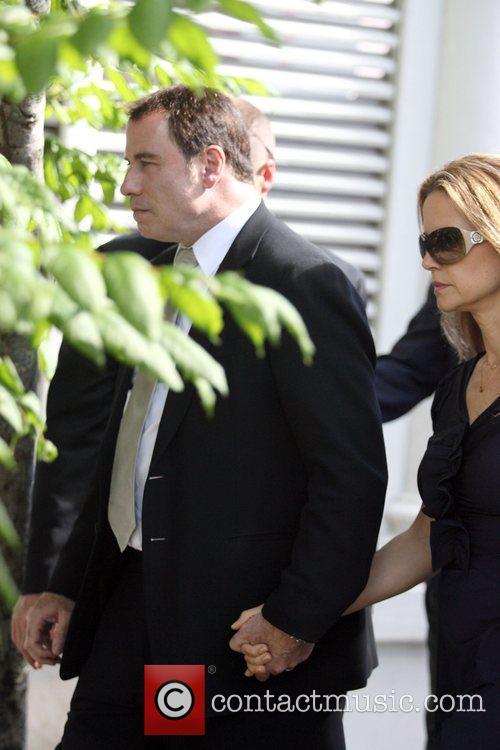 John Travolta and Kelly Preston make their way...