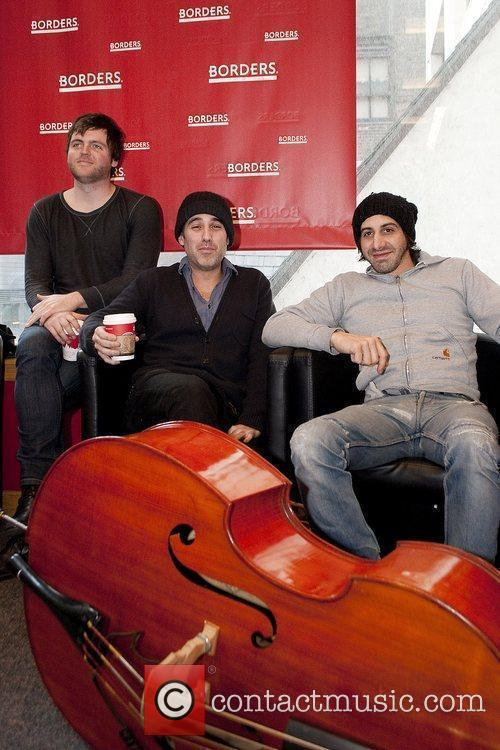 Joshua Radin (center) signs and performs songs from...
