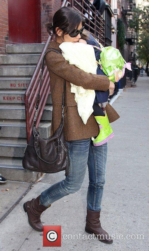 Katie Holmes carrying her daughter Suri as they...