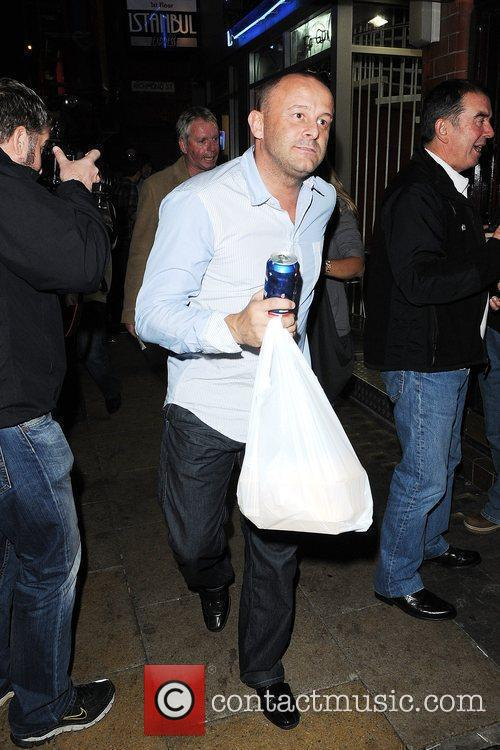 Kerry Katona and husband Mark Croft carrying take...