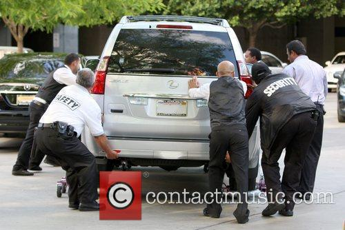 Security guards push a vehicle of a celebrity...